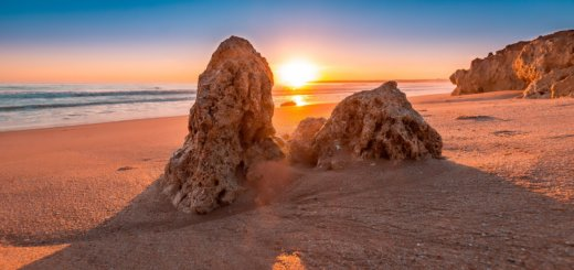 Sonnenstrahlen durch Felsen am Strand in Portugal