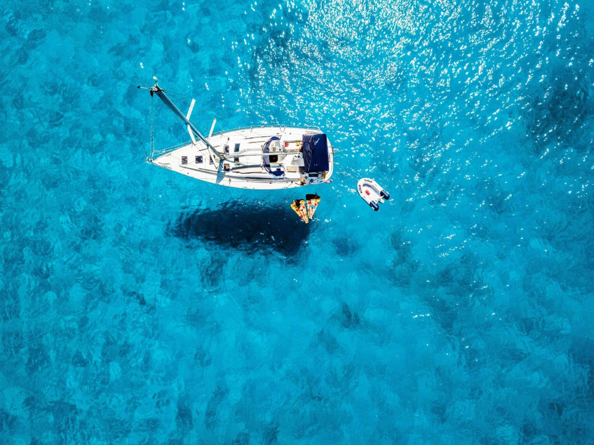 Couple enjoying the water by their anchored white sailboat