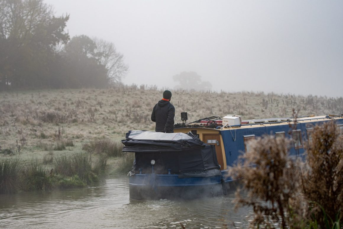 Man driving a narrowboat on a canal through frosty fields
