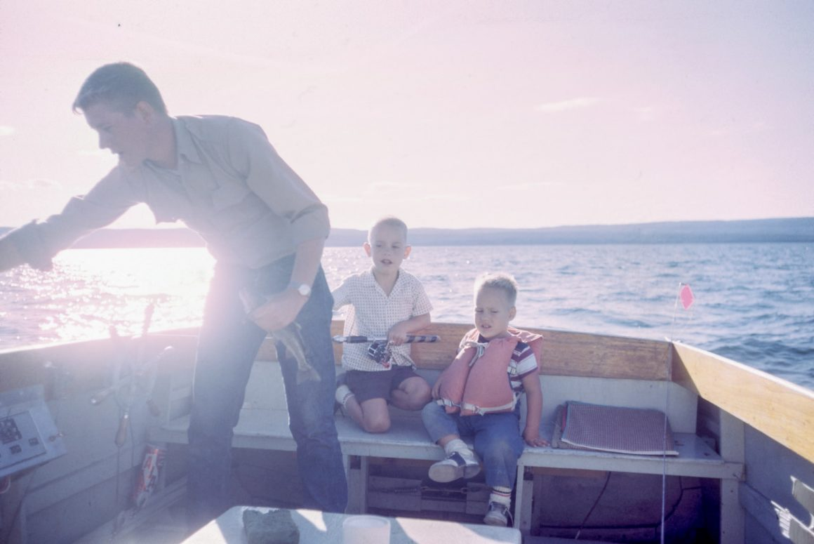 father and 2 children on a boat at sunset
