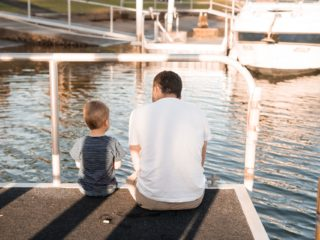 Father and child sitting at the edge of a marina