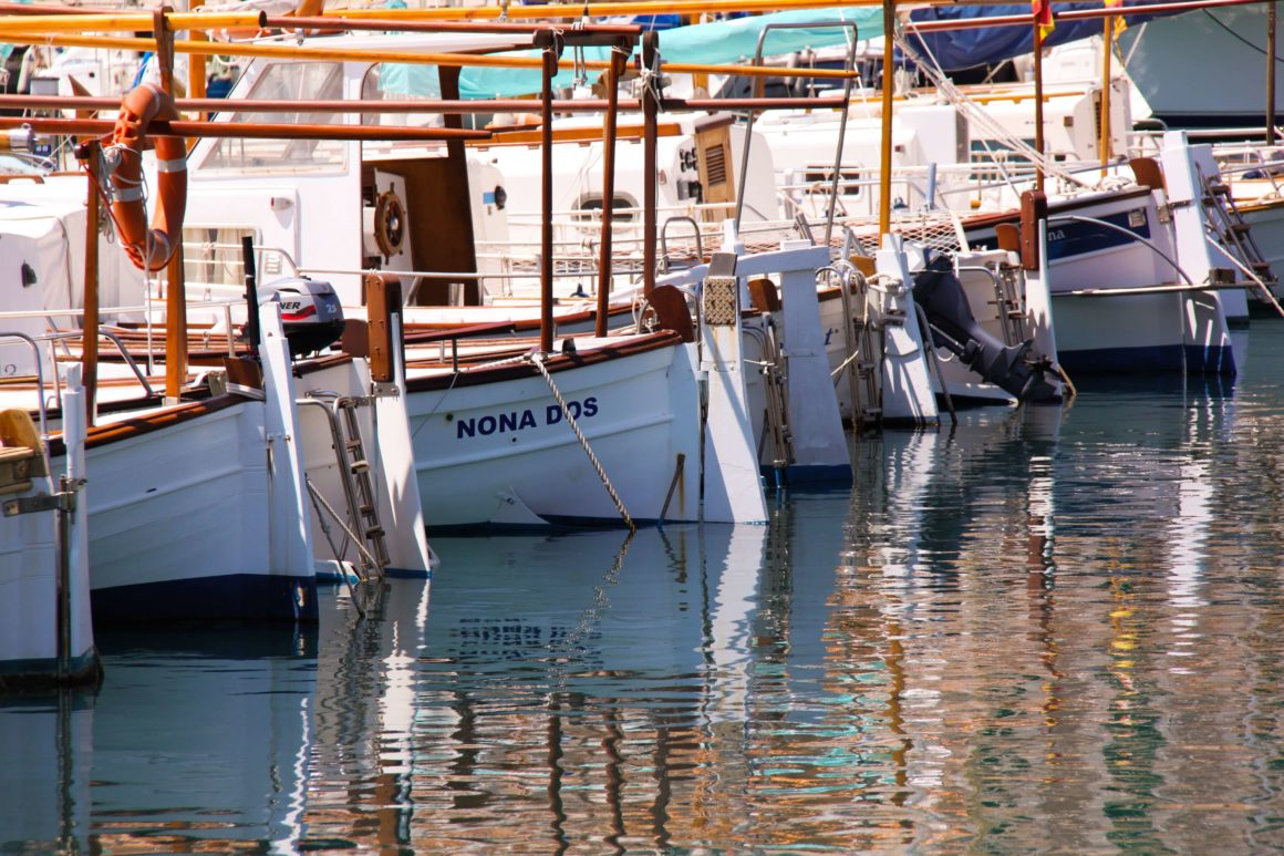 small white, wooden boats lined up in a marina in Mallorca