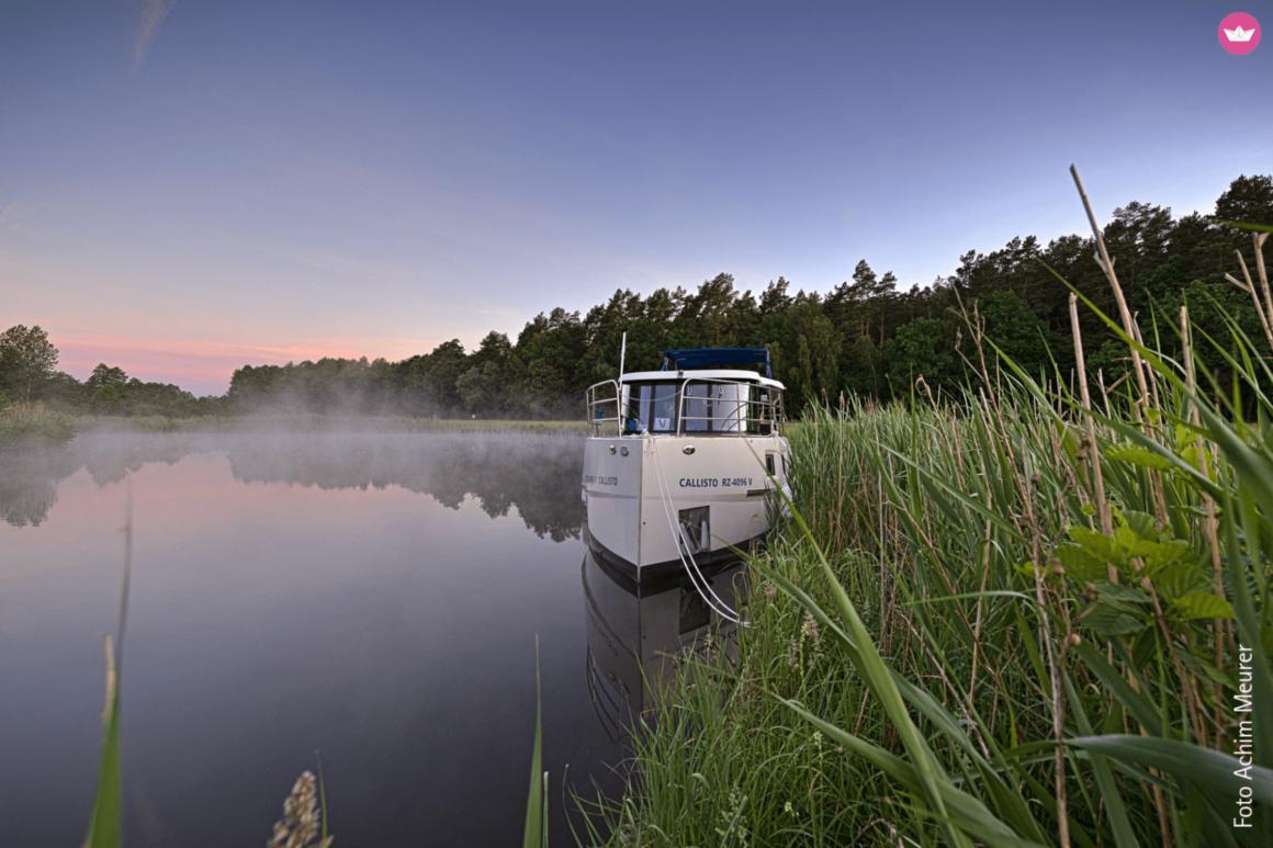 Boot op een meer bij valavond