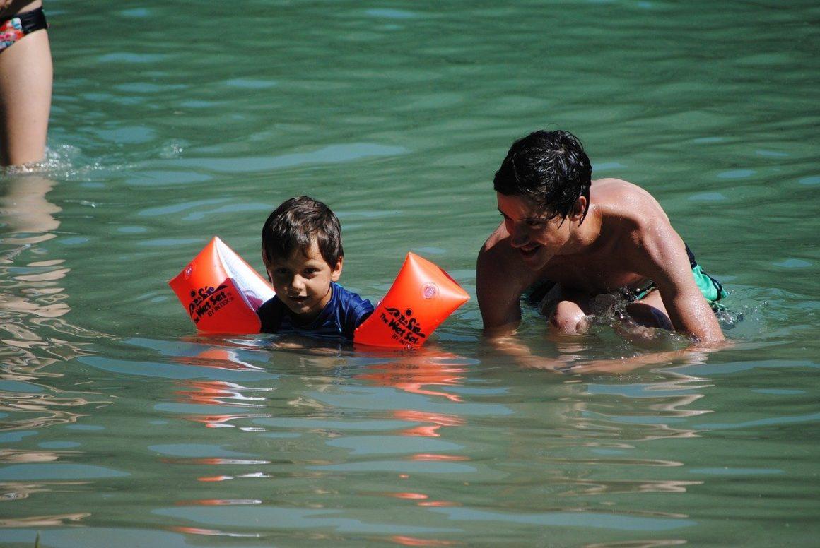 Kleuter zwemt met zwembandjes met broer