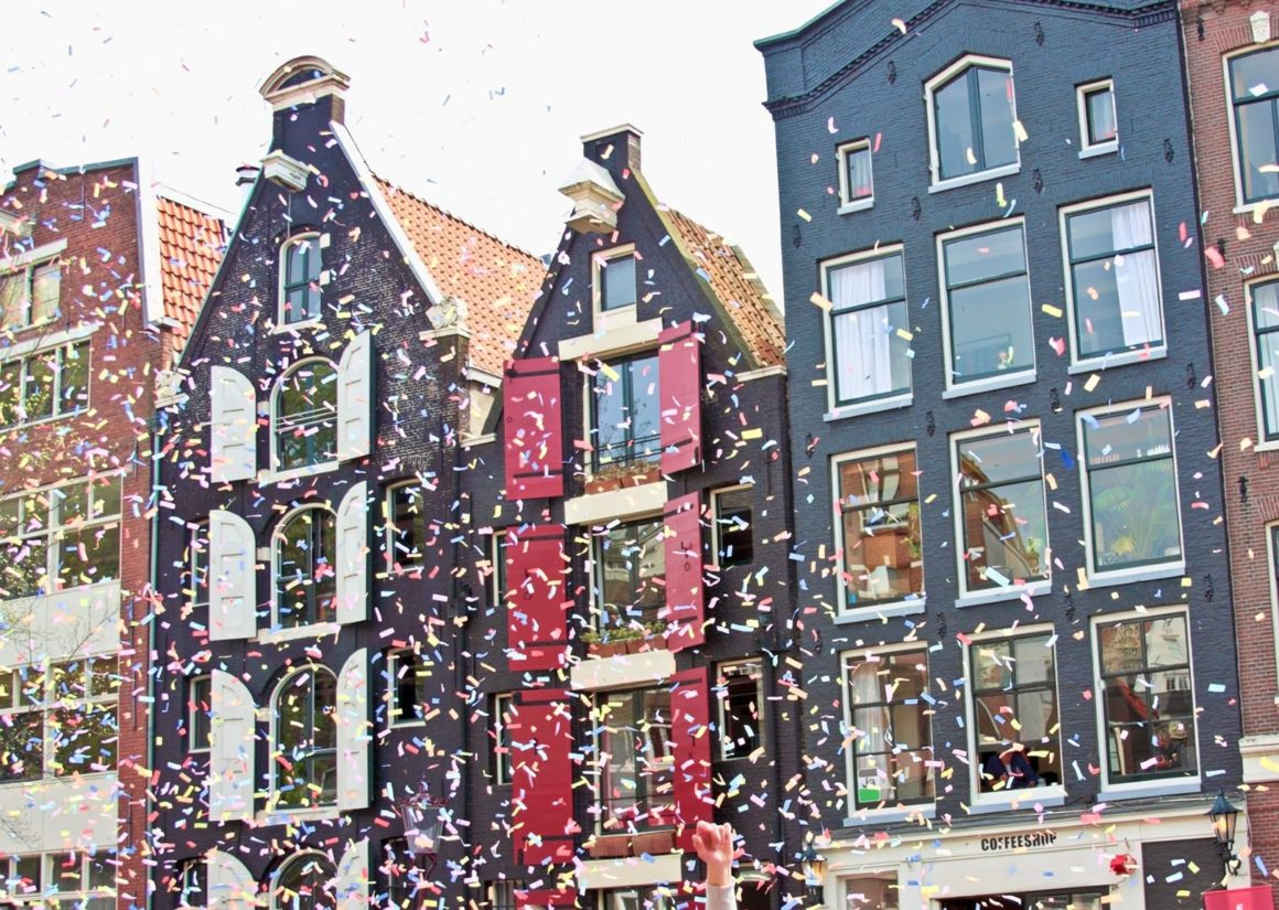 Confetti in de lucht in Amsterdam met huizen