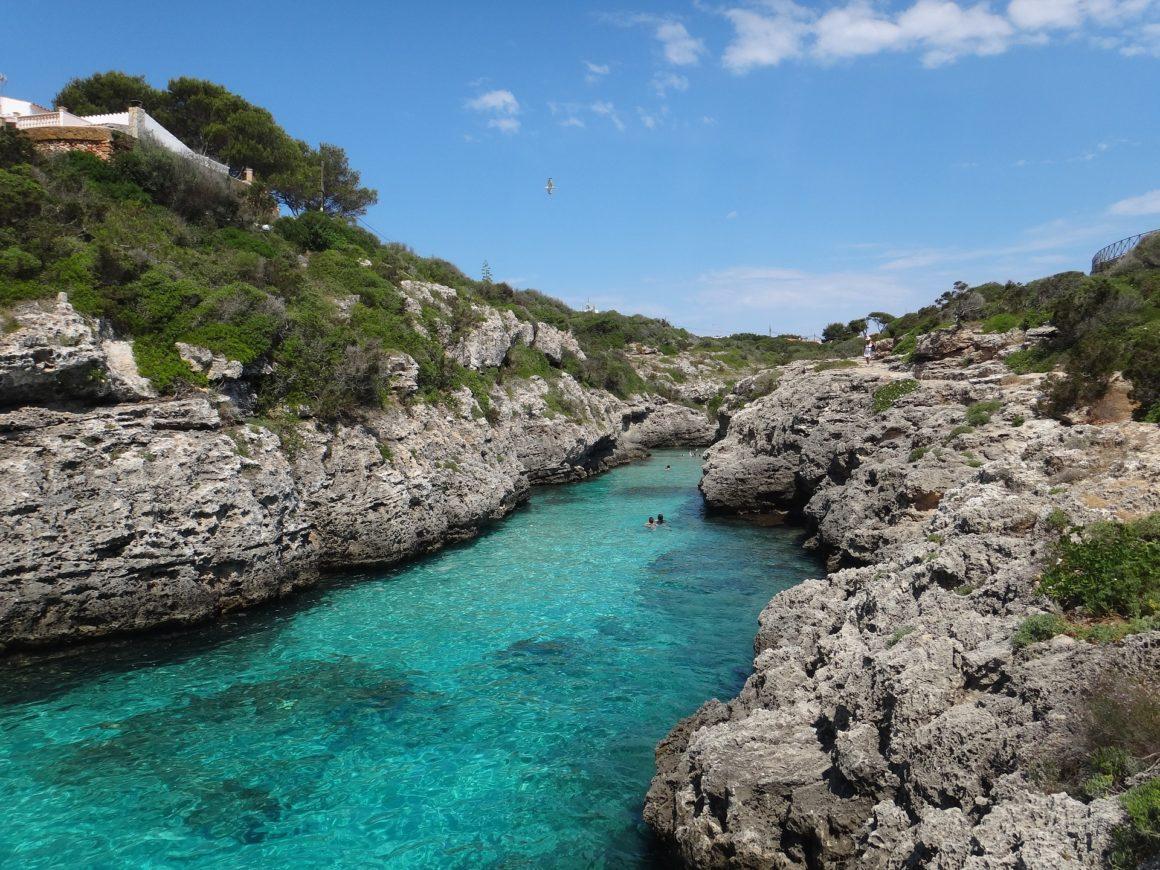 Een baai op het eiland Menorca met helderblauw water en rotsen