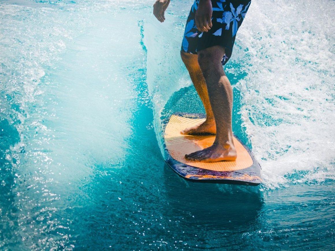 Pernas de um homem em cima de uma prancha de surf. Ao fundo, o mar e as ondas são azuis.