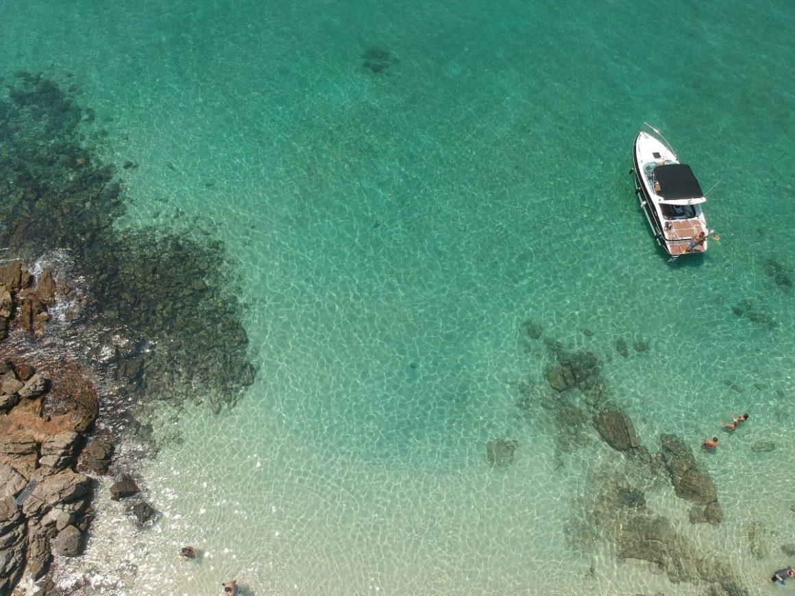 Imagem aérea que mostra um barco branco, com teto preto, dentro do mar azul-turquesa. É possível ver algumas rochas dentro da água.