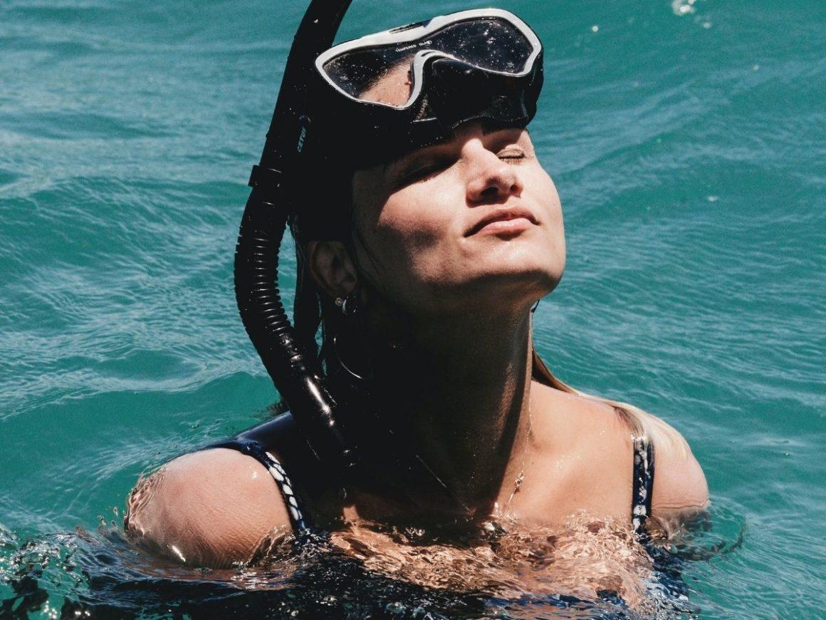 Mulher com o rosto parcialmente coberto por máscara de mergulho, dentro do mar azul.