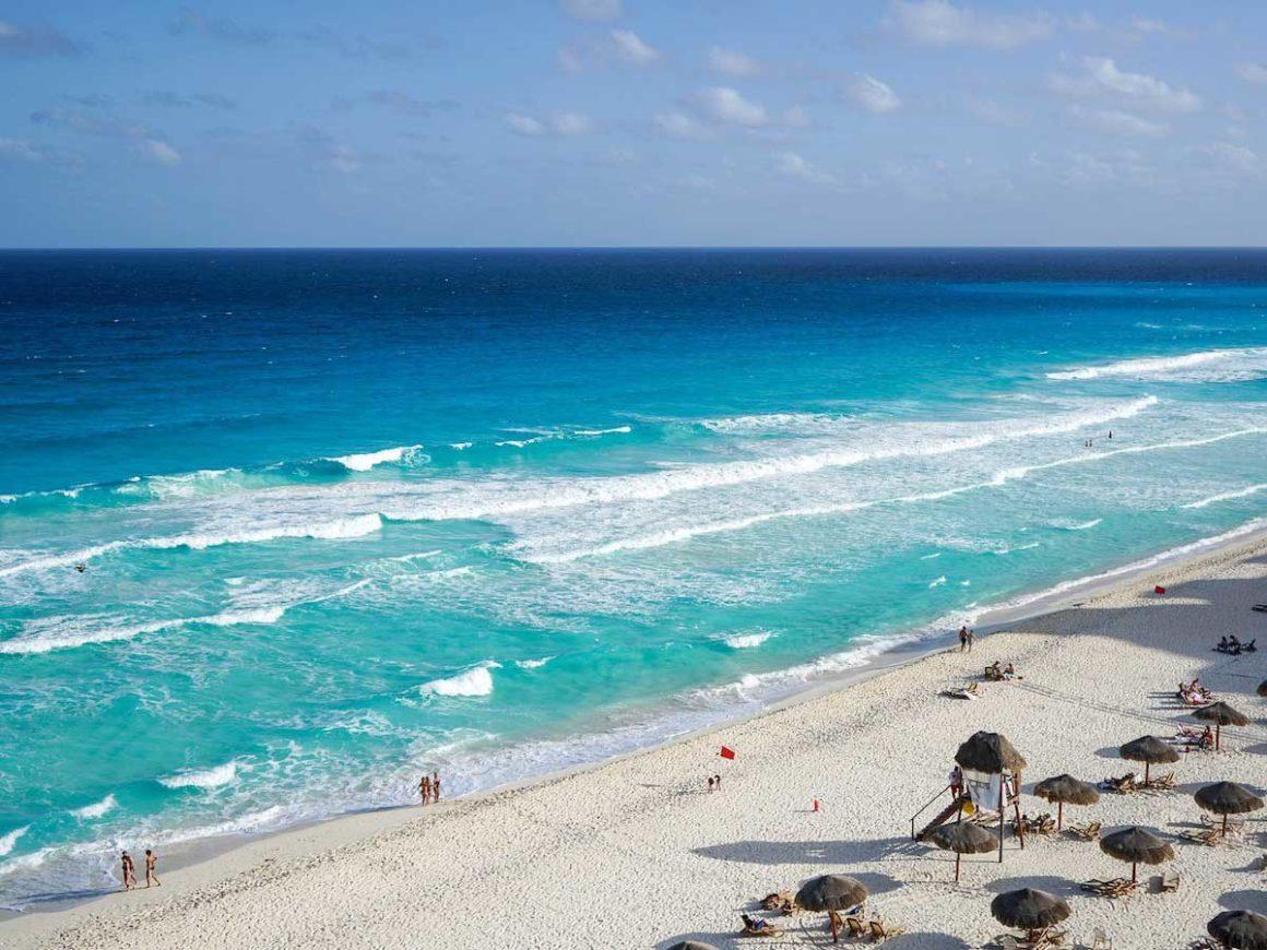 Praia de areia branca e mar azul. Na faixa de areia é possível ver guarda-sóis de cor marrom e algumas pessoas que estão paradas diante do mar.