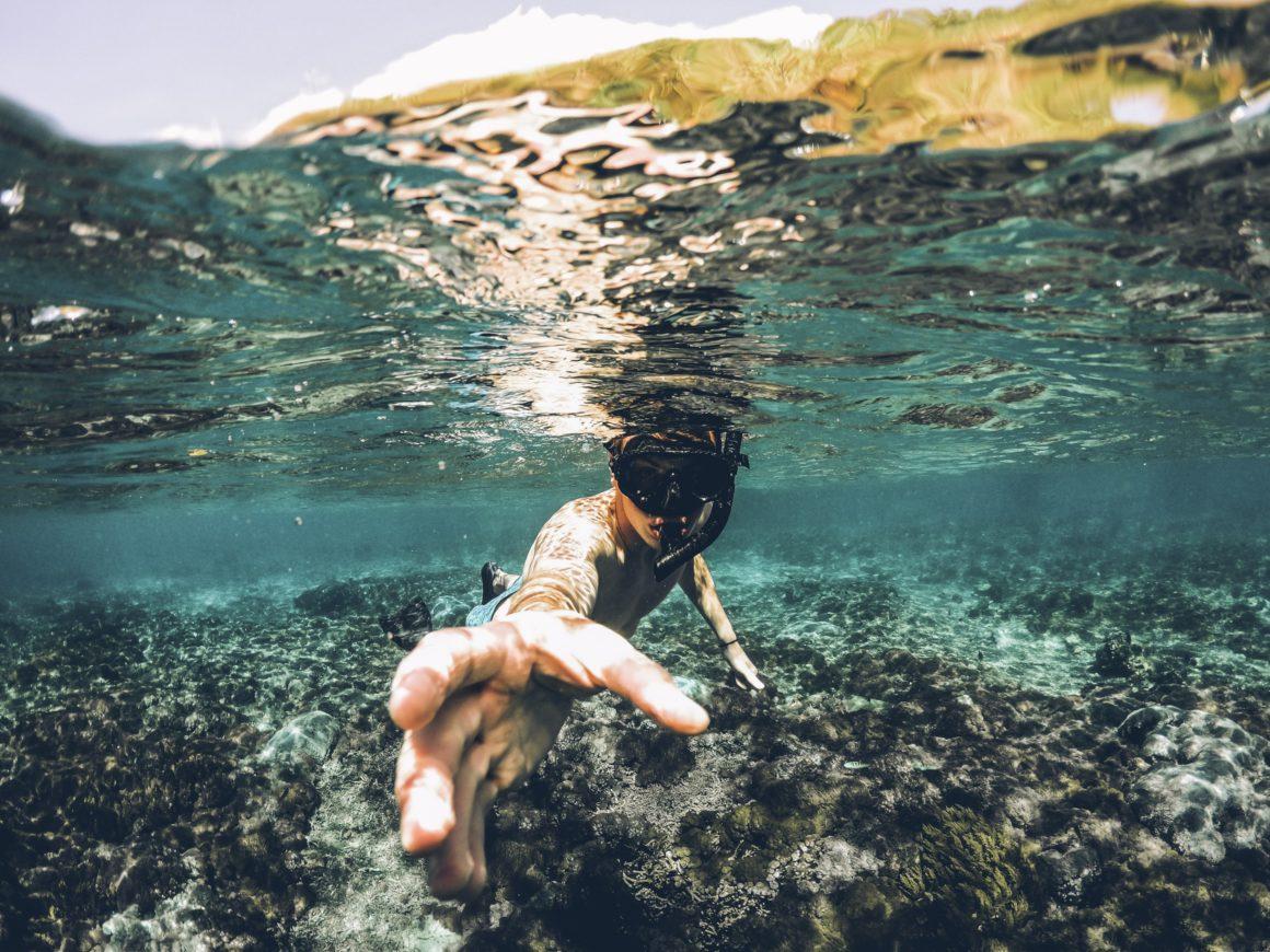 Homem com máscara de mergulho debaixo de águas transparentes. Ele tenta tocar na câmera que tira sua foto. É possível ver os arrecifes ao seu redor.