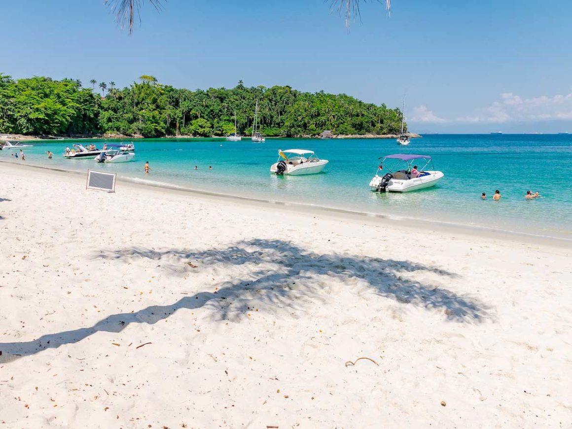 Praia de areia branca, com a sombra de um coqueiro na areia, e o mar verde azulado. É possível ver quatro barcos dentro da água e alguns banhistas também.