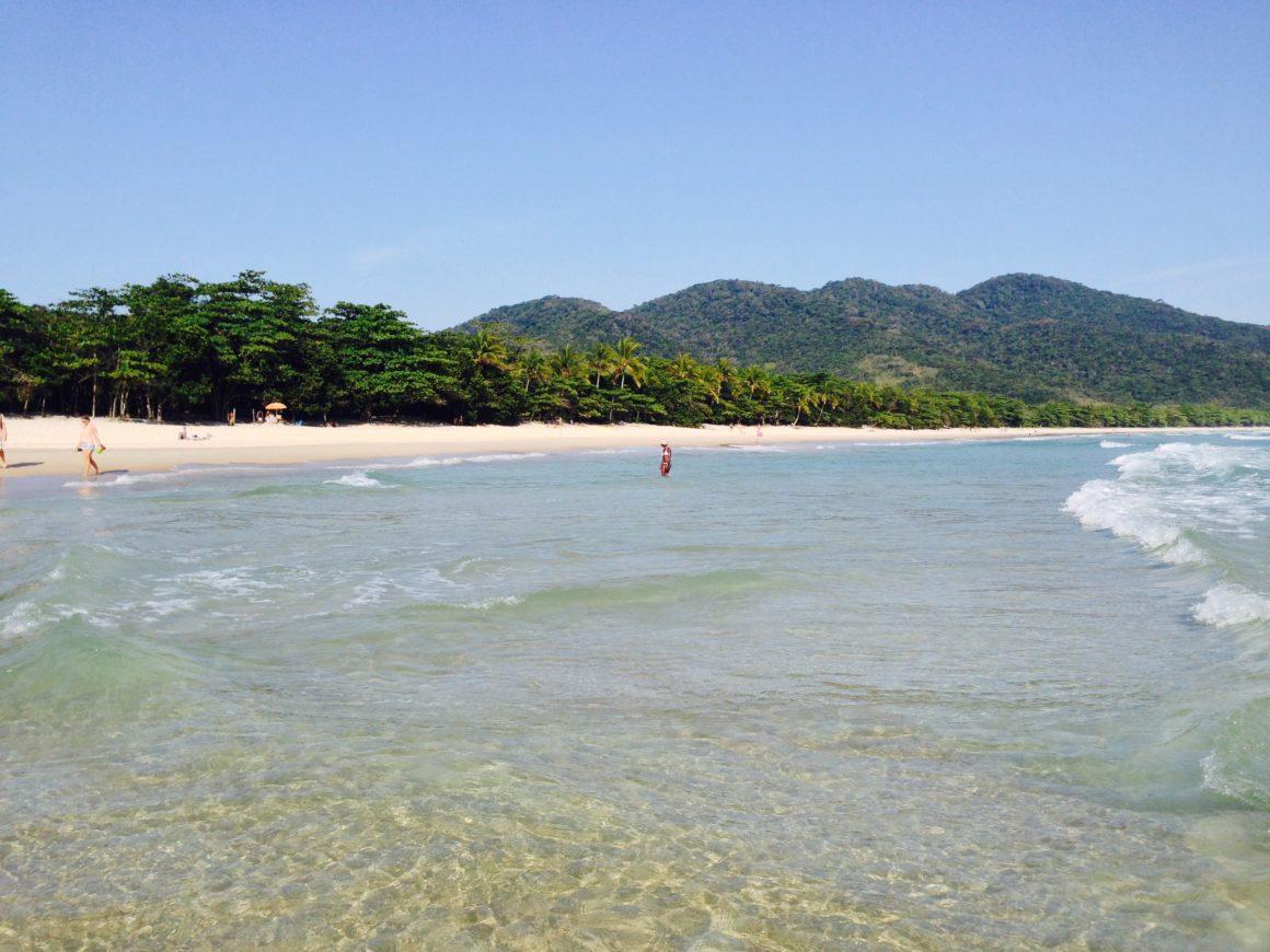 Praia de águas transparentes, com pessoas caminhando dentro e fora do mar.