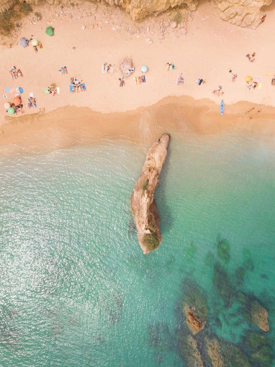 Foto aérea de uma praia com mar esverdeado e areia levemente avermelhada. Grupos de pessoas estão deitados na areia, alguns deles com guarda-sóis abertos. É possível ver algumas rochas dentro do mar.