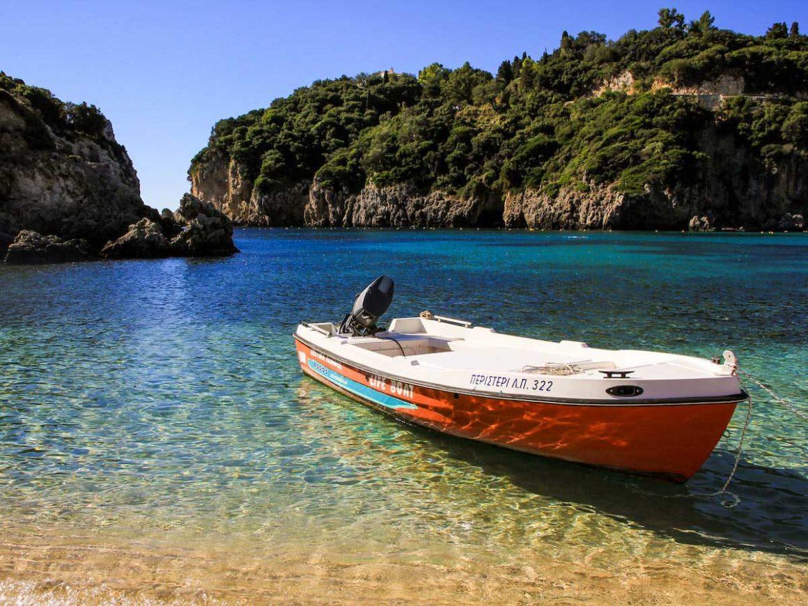 Um pequeno barco de casco vermelho e interior branco flutua na orla de uma praia. É possível ler as palavras life boat e também algo escrito em grego. Ao fundo, o mar vai passando de verde claro para azulado, e no horizonte se vê um paredão de falésias cobertas por vegetação densa.