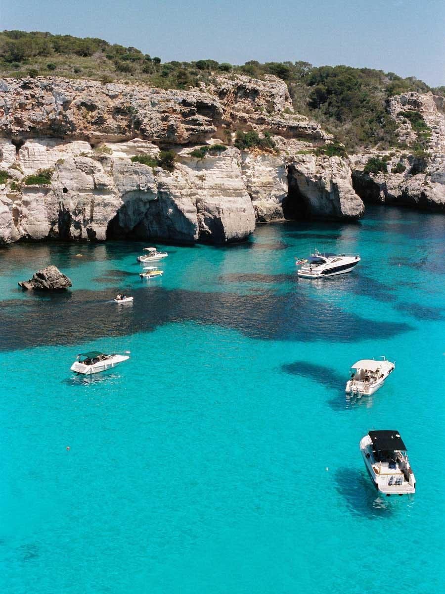 Falésias de cor clara cercam um mar em dois tons de azul. Dentro do mar estão quatro barcos menores à esquerda e três barcos maiores à direita.