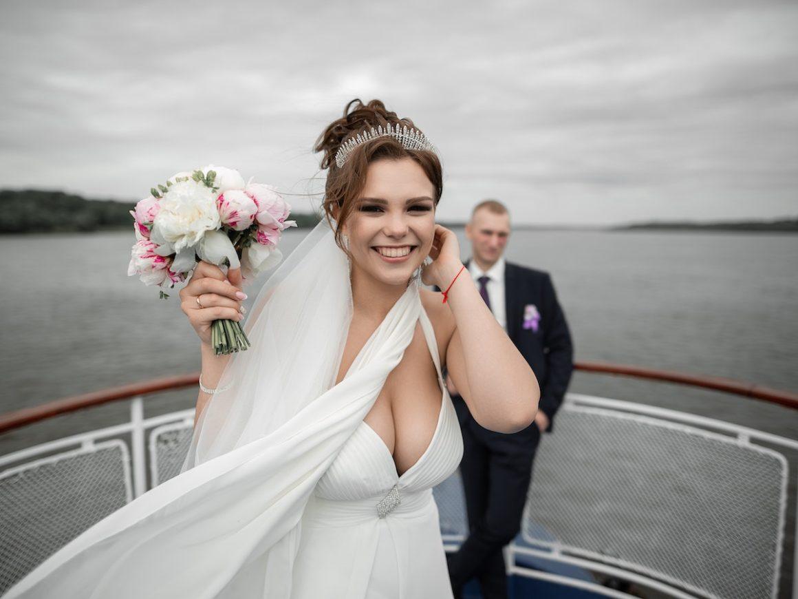 Mulher vestida de noiva com um buquê de flores brancas e rosadas na mão direita sorri para a foto. Em segundo plano está um homem vestido de terno azul escuro, com uma flor roxa na lapela. Ao fundo é possível ver que eles estão em um barco e também a cor da água, que é escura.