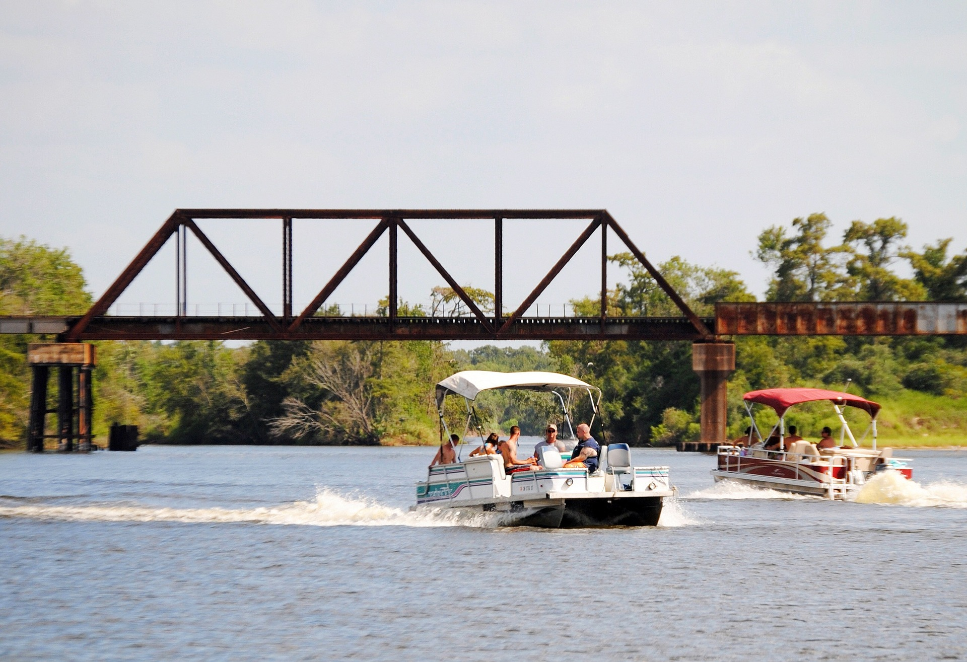 Two Pontoon Boats Rentals Cruising Under a Bridge
