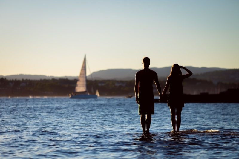 Sailing couple standing in the water