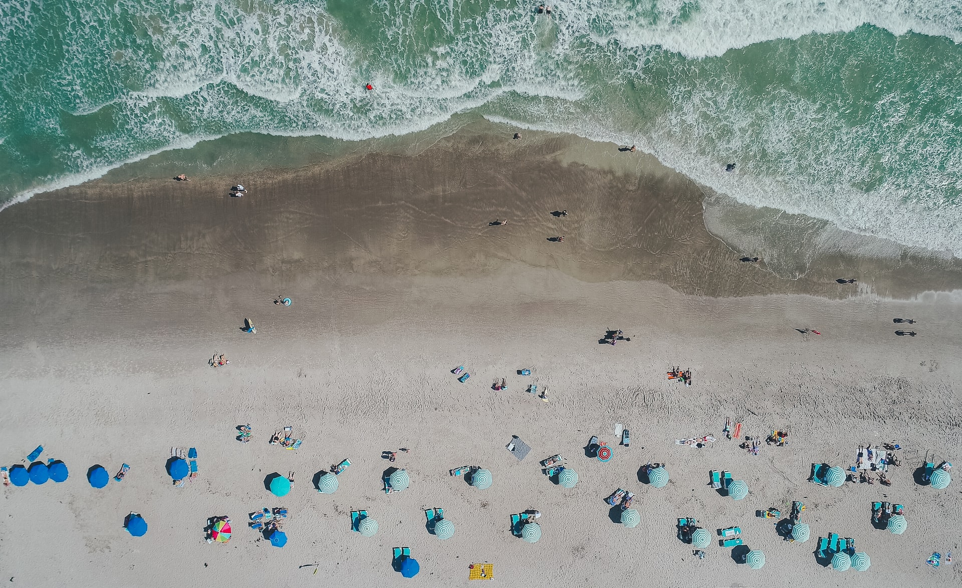 cocoa beach viewed from above with lots of parasols and waves
