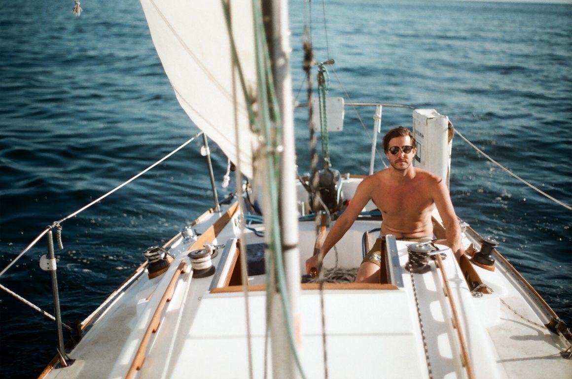 Man navigating a sailboat